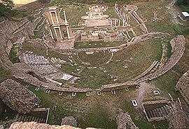vista aerea del teatro romano: si notano la cavea, la scena e, sullo sfondo, i resti del complesso termale